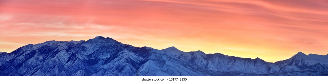 Sunrise of Winter panoramic, view of Snow capped Wasatch Front Rocky Mountains, Great Salt Lake Valley and Cloudscape from the Mountain view Corridor Highway. Utah, USA.