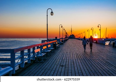 Sunrise at the wooden pier (molo) in Sopot, Poland and a unrecognizable walking couple