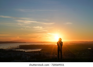 Sunrises defocused silhouette a person in bright light with abstract effect over Auckland from top Mount Eden