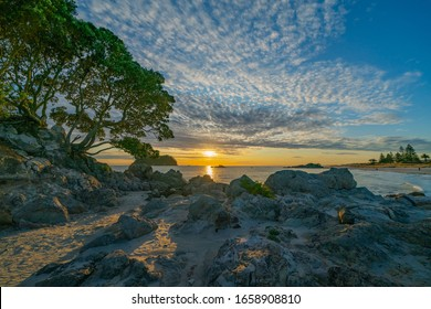 Sunrises over distant horizon along beach from rocky foreground under altocumulus cloud formation on Mount Maunganui Main Beach.
