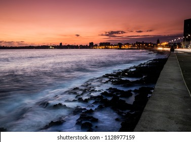 Sunrises over Historic Havana's Malecon walkway.