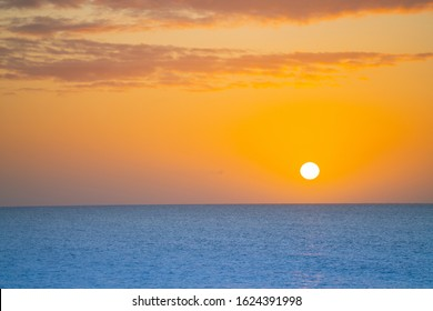Sunrises over horizon along Deal waterfront golden glow over blue sea as abstract background image.