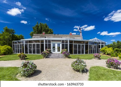 A sunroom attached to a red barn with many beautiful flowers around the building