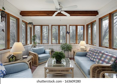Sunroom with wood ceiling beam and wicker furniture