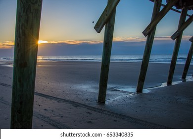 The sun's rays behind the piling of a fishing pier with the ocean in the background