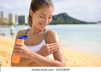 Sunscreen fitness woman applying suntan lotion. Sporty Beautiful happy asian woman with suntan cream applying sun protection before fitness running on beach during summer. Waikiki, Oahu, Hawaii.
