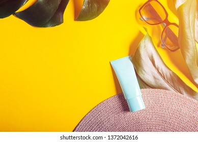 Sunscreen product on yellow background, flat lay. Spring and summer protection against the Sun