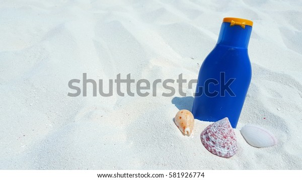 Sunscreen and shells on the white sand beach background summer holidays