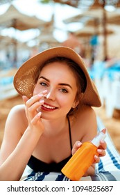 Sunscreen / sunblock. Woman putting solar cream on nose smiling  beautiful summer day. Skincare. Girl applying sun cream
