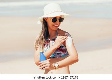 Sunscreen, sunblock. Woman putting solar cream on shoulder smiling beautiful summer day. Skincare. Girl applying sun cream