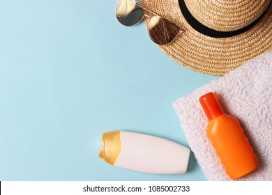 sunscreen, towel, hat, glasses on a colored background. Cosmetics for safe sunburn. top view, flatlay