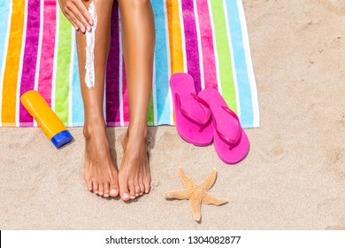 Sunscreen woman applying sun tan cream sunblock lotion on legs with bottle, flip flops and sea star on colorful beach towel on sand. Suntan protection on beach summer travel vacation. female model.