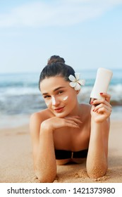 Sunscreen woman applying suntan lotion showing bottle. Beautiful smiling happy woman with suntan cream  lying on beach.  Skin care. Body Sun protection.Sun cream on face.