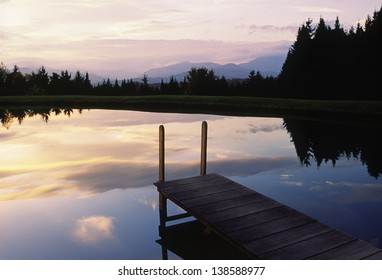 Sunser over a pond with a dock, Stowe, Vermont, USA