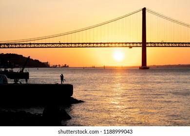 Sunset at 25 april bridge in Lisbon