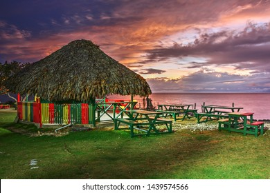 Sunset at 3 Dives point in Negril, Jamaica. A wooden hut, featuring Jamaican colors sits on top a a high cliff popular with jumpers.