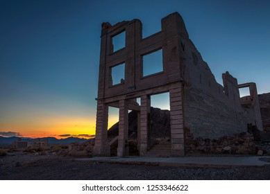 Sunset above abandoned building in the town of Rhyolite, Nevada. This ghost town is located in Nye County among Bullfrog Hills near Death Valley.
