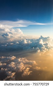 Sunset above clouds illuminated by the rays of the sun from airplane window. Sunset with a height of 11 000 km. View of the beautiful cumulus clouds at sunset from an airplane window, true colors