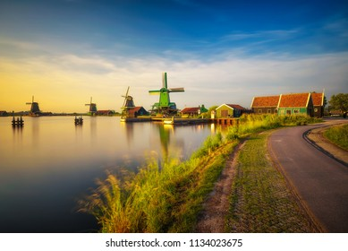 Sunset above historic farm houses and windmills in the beautiful holland village of Zaanse Schans near Amsterdam in the Netherlands. Long exposure.