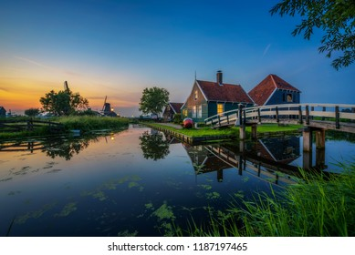 Sunset above historic farm houses and windmills in the holland village of Zaanse Schans near Amsterdam. Long exposure.