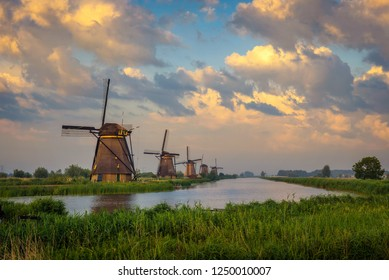 Sunset above historic windmills and a river flowing by in Kinderdijk, Netherlands.