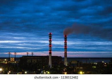 Sunset above two smokestacks from a coal thermal power station. Smokestack emissions and air pollution at an Industrial district