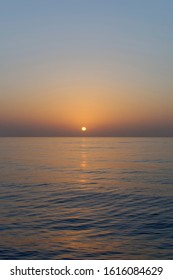 Sunset across calm water as the sun starts to dip over the horizon as a Vessel transits through the Bay of Benin in West Africa,