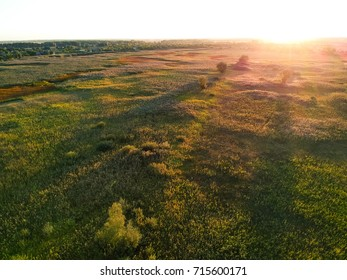 Sunset aerial view on grass field before autumn in Europe