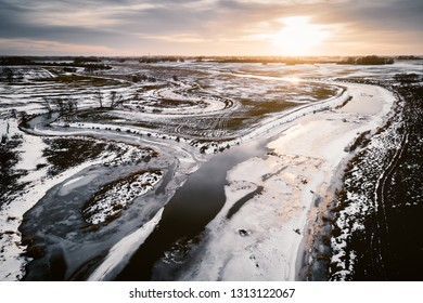Sunset aerial view of two rivers with cracked ice in winter time.