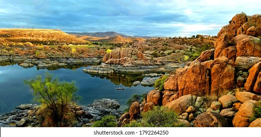 Sunset after late summer storm at Lake Watson, Prescott, Arizona with golden rocks over still blue skies with sky reflection
