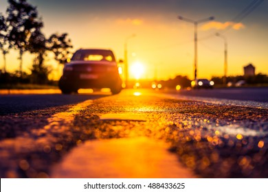 Sunset after rain, the car parked on the roadside and headlights of the driving cars on the highway. Close up view from the level of the dividing line, image in the orange-purple toning