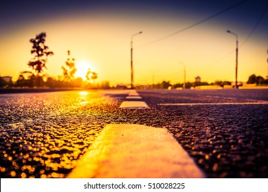 Sunset after rain, the empty highway. Wide angle view of a close-up from the level of the dividing line, image in the orange-purple toning