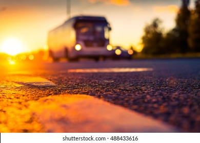Sunset after rain, the headlights of the approaching bus on the highway. Close up view from the level of the dividing line, image in the orange-purple toning