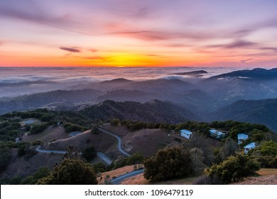 Sunset afterglow over a sea of clouds; winding road descending through rolling hills in the foreground; Mt Hamilton, San Jose, south San Francisco bay area, California