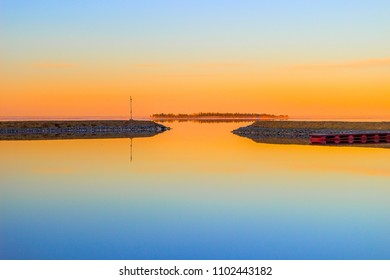 Sunset against the background of the lake and pier for yachts