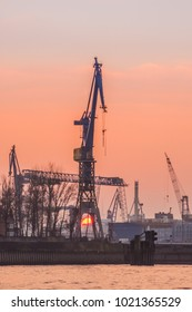 Sunset against the silhouettes of the port cranes of Hamburg.Blurred background.