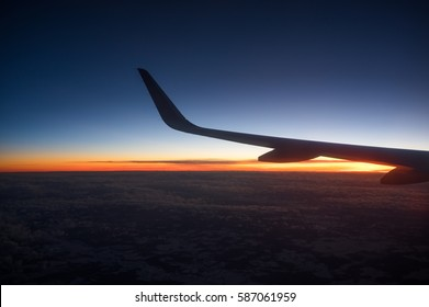 Sunset from the airplane window with the jet wing