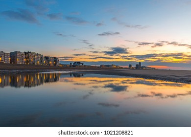 Sunset along the North Sea beach of Ostend city with a skyline reflection, West Flanders, Belgium.
