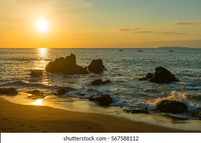 Sunset along the Pacific Coast of Costa Rica with rocks, waves and a yellow sun.