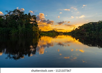Sunset in the Amazon River Rainforest Basin with a reflection in a lagoon connected to the Napo River inside the Yasuni National Park, Ecuador, South America.