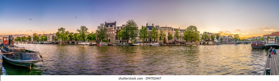 Sunset in Amstel.  A panorama of most famous canal of Amsterdam with boats, old bridges, traditional dutch houses and lovely  houseboats.