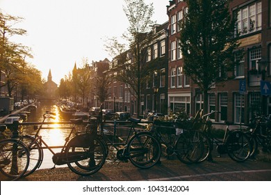 Sunset at Amsterdam channel with bikes and old houses