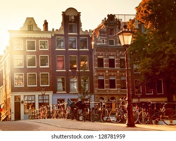 Sunset in Amsterdam (Netherlands), many bikes on a typical little bridge over a canal in Jordaan neighborhood