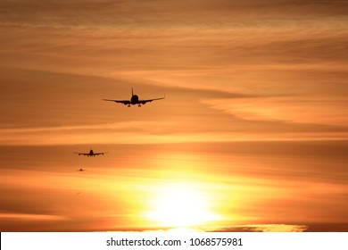 Sunset arrivals - a lineup of planes on final approach to the airport