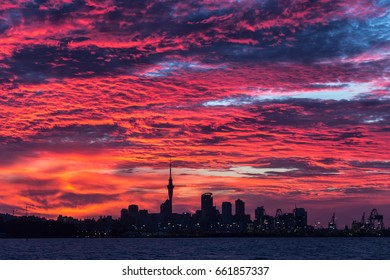 Sunset of Auckland skyline, New Zealand, with stunning red clouds.
