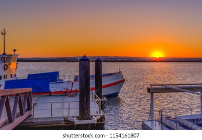 Sunset in Ayamonte over the Algarve across the Guadiana River which marks the border of Spain and Portugal. The ferry which takes tourists and locals across the river is in the foreground