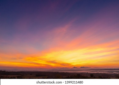 Sunset background with wonderful golden yellow sky, Amazing purple and orange sky in evening during the sun going down above the mountain at countryside, Chae Hom District, Lampang, Thailand.
