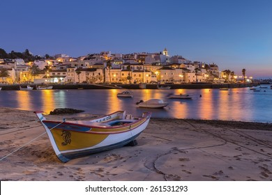 Sunset in the bay of Ferragudo, Portimao. Fishing boat on the shore.