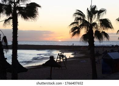 Sunset at beach and Atlantic Ocean panorama in holiday resort Playa de las Americas on Canary Island Tenerife, Spain