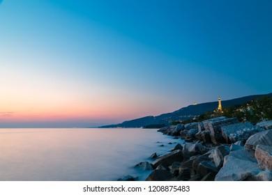 sunset at the beach below the lighthouse of Trieste, Friuli Venezia-Giulia, Italy
